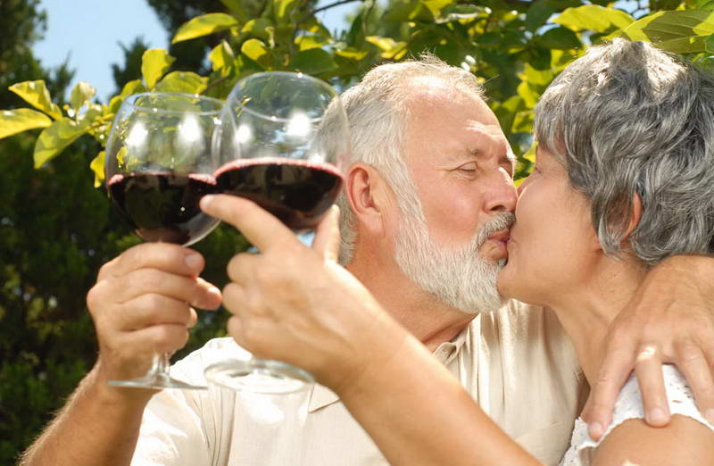 hunter valley half day wine tours - older couple holding Hunter Valley wine and kissing in the vines